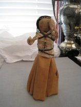 Image of Indian doll with bark skirt and beads.