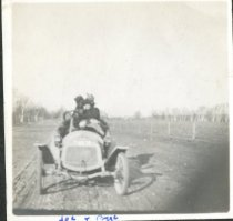 Image of Photograph of Byge and Joe (the dog) in a small automobile.