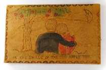 Image of Leather postcard with a picture of a couple sitting under an apple tree.