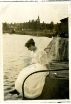 Image of Photograph of a woman sitting on a dock.