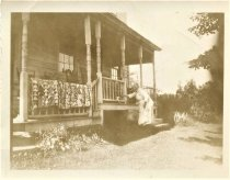 Image of Folder 11 - Old woman standing in front of house, petting cat