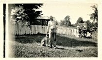 Image of Folder 34 - Henry K. Fink on farm, standing with dog, 1936