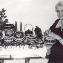 Image of Print, Photographic - Mrs. J. Franklin Suiter with her woven baskets Mrs. J. Franklin Suiter with her weaving