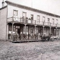 Image of Print, Photographic - Group portrait of men, women and children in front of the Queens Hotel on Yale Road East
