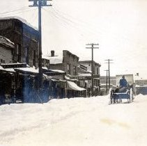 Image of Print, Photographic - Street level view of commercial buildings and businesses on Wellington Avenue following a winter snow storm.