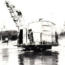 Image of Print, Photographic - View of large caterpillar-type dragline travelling in middle of fast moving river.
