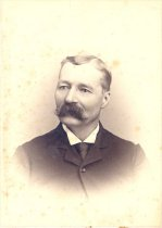 Image of PO.001.0059 - James (Jim) Taylor, one of the Founders of Fall City in 1869 by Boyd, Seattle. Cabinet photo portrait, scalloped edges 4 sides, black and white.  Man wearing dark pin-stripe suit, coat buttoned at top button, black tie, white shirt with white collar with front sides only turned down into triangle. Head turned slightly to left. Hair parted on left side, with slight wave in front. Short hair. Has moustache, thick, dark, wide with ends curled upward. Uncle of William H Taylor and one of founders of Fall City in 1869. Came in 1869 with the Boham Brothers and built log house that David Taylor Family lived in.  Photo by Boyd, successor to Judkins Co, Second and Columbia.