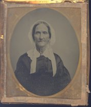 """Image of PO.002.0049 - Daguerreotype picture of Mrs. Moorehead Anderson with breast pin on. She was great-grandmother of James Rees, father of Jerry Rees. 2""""x3"""" oval in frame of the case.  The picture is of an elderly lady, with a white bonnet on her head. The ties fall over her shoulders, over the white collar of her dress. Her dress is a dark color. The case has a hard frame, and the cover is embossed design with doves in the center. It folds like a small book and has two metal hooks for closure. Inside has a velvet lining and the frame is of a gilt color."""