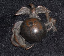 """Image of 044.005.a - Lester Burn's Marine Corps Insignia button. a. Large button, screw-on type, --world globe with maps of No. and So. America on globe: anchor with rope entwined in ring at top and part of anchor: eagle with outspread wings on top of globe. 1 1/2"""" long x 1 1/2"""" wide. BRONZE"""