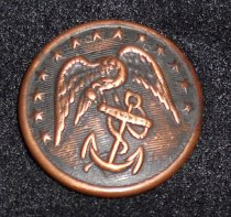 """Image of 044.005.b - Lester Burn's Marine Corps Insignia button.  Large round bronze button, with eagle (head bent down), wings outspread: chain entwined around anchor: stars around top edge of button. Raised edge around button. 1 1/4"""" wide diameter."""