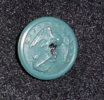 """Image of 044.005.e - Louise Burn's Lady Marine Corps Insignia Button.  Green button, 5/8"""" diameter, eagle with head bent, wings outspread, on anchor with chain entwined in ring at top and part of bottom, line of small stars around top edge; narrow rim around edge."""