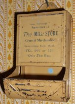 """Image of 074.577 - Snoqualmie Falls Lumber Co mill store match holder.  Metal Match Safe (dispenser or holder) Yellow brown in color.  You put a box of wooden matches in the top and take out of the bottom as needed.  The writing on the container says """"Your Patronage is appreciated at the Mill Store General Merchandise, Snoqualmie Falls, Wash.  Tel 561 or 131 'Only the Best'""""  Facing the front on the back near the top says """"Mnf'd by PN Co, Fulton, Ill, USA"""" Color of writing is medium blue."""