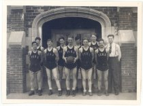 Image of PO.015.0317 - Fall City High School Basketball Team; 1938.  Boys basketball team in uniforms with coach standing in front of front door of Fall City High School. Boy in center front is holding a basket ball. Dark uniforms, light color bands around edge of shorts and light color letters on front of athletic shirts FCHS.  Left to Right- Front- Mitsu Sato, Nels Nelson, ? Baxter, Harold Donnelly, Donald McGill Back- John McKibben, Byron Coppers, Howard Sorensen, Dick Dodge Coach- Tom Mus