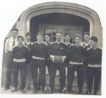Image of PO.015.0362 - Fall City High School Basketball Team. 1937.  Nine young men in basketball jersey sweater suit uniforms. The boy in front is holding a basket ball. They are standing in front of the school with coach Tom Mus. Picture has been cut to the shape of arched entry.