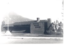 Image of PO.015.0623 - Snoqualmie Valley Historical Museum building 320 North Bend Blvd (later Bendigo Blvd) S North Bend with Indian style canoe hanging on front.  Flagpole in front of building.  Mount Si in left background