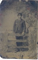 Image of PO.002.0052 - Tintype of James Rees, first husband of Alice Borst. Taken when he was Captain of one of the Snoqualmie River boats. Background on right are ferns, behind wood fence. Gate has 3 rails, horizontally, flowers and shrub in foreground in front of fence posts.  James Rees is dressed in dark suit and cap with black leather band, white shirt, bow tie. Has moustache and dark hair.  Handkerchief in right pocket. Coat buttoned in front with top and 2nd button. Standing with left hand on top rail of gate.