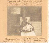 Image of PO.002.0058 - Euphemia, grandmother of Jerry Rees, on her 90th birthday, holding her birthday cake. Photo taken on porch of house where her daughter-in-law lived. Home of Alice Borst Rees Rachor in North Bend.  Euphemia is sitting in chair on front porch, near front door of house. Wears dark dress and white apron. Holds cake with 90 candles on it.