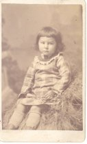 Image of PO.002.0059 - Eva Borst daughter of Kate and Jeremiah Borst.  Looks about 5 years old sitting on a straw pile.