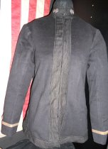 Image of 842.003.a - US Navy Uniform Jacket.  Black with gold trim on cuffs and gold star at wrist.  Made out of wool with linen or cotton lining.  Black trim around neck and down front and around bottom, anchors at each side of front neck, side pleating hook and eyed.  Number 1546 and c.280 hand written.