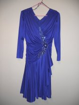 """Image of 937.001 - Cleo Soister's royal blue dress. Made of polyester. High V-neck. Zips down the back. 3/4-length sleeves. Gathered at shoulders. Ruching on top. Gathered in blue and silver sequined flowers from bottom of V down to waist. Skirt extends to below the knee. Label reads """"David Rose."""""""