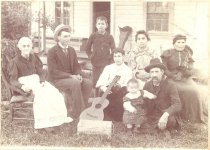 Image of PO.002.0054 - Family Group of Borst-Rees Members  Scene of family group and friend, Clarence Kinsey on lawn in front of house. 5 members sitting in chairs in semicircle with young boy standing, man sitting on grass and holding musical instrument leaning against hand of young girl in front row.  Wooden box on grass in front of the group with rope attached at top of right end. Box stamped on side Medallion Black Pepper, 4 dozen, 1/4 lb. High Chicken wire fence in back of group. Front door of house open, wooden bench on porch on left of door, wooden porch and wooden steps.  Family Left to Right: Grandma Euphemia Rees, Clarence Kinsey, Bud Borst standing, Eva Borst in white blouse sitting in front row, Mrs. Alice Borst Rees in back in striped dress, Mrs. Kate Borst on far right, baby Eden Rees, James Rees holding baby.  Bud, Eva, Alice Borst are children of Jeremiah Borst and his first wife Mina.  Kate Borst is 2nd wife of Jeremiah Borst. James Rees husband of Alice Borst Rees. Clarence Kinsey, brother of photographer Kinsey family in Snoqualmie. Euphemia Moore Rees, Mother of James Rees.
