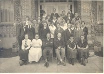 Image of PO.003.0037 - Class of North Bend High School, 1917-1918.    Black and white photograph.    Taken in front of brick school.  Front row sitting.  4 rows standing on steps.  School built 1915, burned March 1967.
