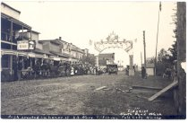 Image of PO.003.0048 - Arch in Honor of US Navy Officers, Fall City, Wash. Siegrist 111. North Bend, Wash.  Arch in Honor of US Navy Officers visit to the Valley with the White Fleet.  Buildings of the businesses in Fall City; several cars are coming down the street to come through the arch. The arch is made with a decorated top, and many flags at the top. The supports on each side are large pedestal type pillars. The sign for the Olympia Bar can be seen at the left as well as the sign for the drug store.  Siegrist 111