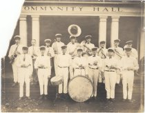 Image of PO.003.0064 - Snoqualmie Valley Band  Band members dressed in all white uniforms, white caps with black bills; standing on steps and walk in front of Snoqualmie Falls Community Hall.  All holding musical instruments, except 2 drummers.  Large drum on side on walk and small drum on stand to left with two drumsticks on drum.  2 pairs of square posts in front of porch entrance, with Community Hall in large black letters across front  Guy Burnham Ted White Ted Rurnham ? Lynn Bill Peterson ? Goodwin Jimmy Edwards Ted Boalch Sam Lee  ? Hume ? Edwards Earl Tibbets Tommy Thompson ? Templeton Joe Brinkley Bob Kelley