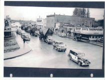 Image of PO.008.0100 - Copy of a newspaper photograph of log truck parade passing through North Bend on North Bend Way with police car in front.  On left is Lee Brothers Grocer, right Thompson's Cafe, Drug Store, Masonic Hall, McGrath's Hotel