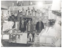 Image of PO.014.0008 - Sale of Reinig Store to Harold Johnson forming Red and White Store.  Otto Reinig, Harold Johnson, Herman Mindrip pictured behind cabinet, boy Mike Alm, son of Sam and Doris Alm.