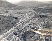 Image of PO.014.0012 - Aerial View of the town of Snoqualmie c 1956-1957. Taken from the North end of town; all the way to the Snoqualmie Pass visible.  Highway 202 can be seen going through the town and on to North Bend. The river is at the left, with trees along the banks. A train is on the tracks at the lower left of the picture. The streets are not laid out in square blocks, some of the blocks are odd shaped, and some are triangular shape.  Open area can be seen east of Meadowbrook Drive.