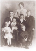Image of PO.014.0016 - Hans Nelson Family.  Fall City Pioneer.  c 1915.  Hans Nelson, Sr. and Mrs Inga Nelson.  Children Standing- Chester, Walter, William Sitting- Helma and Hans (baby).  Man and woman with five children.  Hans and Inga Nelson.  Hans holding baby Hans.  Helma, the little girl is leaning against her father's knee.  The three boys are Chester, Walter, and William.  Two children were born later.  Ivar and Nels.   The lady is dressed in a light color, long dress.  It has high neckline, ruffles of lace to the shoulder.  She is wearing a large locket.  The small children are dressed in white and the boys in dark suits.  Mr Nelson is wearing a suit with white shirt and tie.