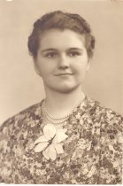 Image of PO.014.0017 - Bernice Thompson Blanchard, daughter of Mabel Damburat Thompson, North Bend Pioneer Family.  Young lady wearing flowered dress with large white flower at throat. She is wearing a double strand of pearls. Her hair is curled and pulled above the ears.
