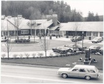 Image of PO.014.0068 - New Salish Lodge and Driveway.  Several cars parked in area, there is a circle of landscaping in center of driveway and large sign with spotlights at right.  The Lodge is made in several different sections, all with windows, with small panes, trimmed in white.  Trees can be seen in the background.  Taken from across the road on hillside.