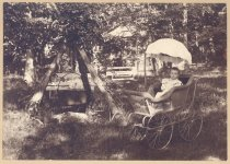 Image of PO.015.0239 - Baby outdoors in buggy next to large wood fire caldron and park benches.