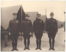Image of PO.015.0381 - Four US Marine Officers standing in front of a long row of tents. WWI era.  Camp made up of tents with no front flaps. Army officers standing at attention at end of row of tents. Medals on uniforms all different design and insignia. Uniforms have form fitting coats with high neckline. Pants are riding breech style and shoes high with laces. All are wearing leggings made of leather so they appear to be wearing boots. Two of the caps are style with bill other two have wide brims.
