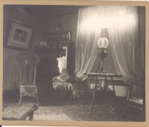 Image of PO.015.0479 - Parlor of Lillie and John Williams. c 1894  Interior of parlor.  Table with tall lamp with globe sitting in front of window with sheer Priscilla style curtains.  Hutch in corner with knickknacks.  Above hutch row of family photos.  Large picture of wicker hanging on side wall next to wicker chair with high back.
