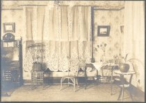 Image of PO.015.0480 - Interior of Parlor. 1890 Parlor.  Walls have wallpaper, wide window has tiered lace curtains.  Three legged table has potted fern sitting on it. Library table has scarf, the lower shelf has books laying on it.  Writing desk at side of window is combination bookcase and desk. Door drops down to make table for writing.  High back wicker chair next to library table.