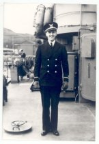 """Image of PO.015.0361 - Ensign John McKibben aboard the """"Atlanta"""" Coast Guard cutter in Alaskan waters. WWII. 1944.  Ensign in full uniform. Uniform is double breasted style with white ribbon around each cuff. He is wearing a light shirt and tie; hat is style with a bill and has coast guard emblem. He is standing on deck of ship."""