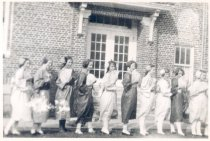 "Image of PO.501.0011 - Ten girls from the cast of ""Miss Cherry Blossom"" standing sideways in front of the North Bend School.   They are dressed in their Japanese costumes- some holding fans, some with flowers over their ears."