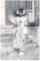 "Image of PO.501.0013.4 - Aileen Reynolds in Japanese Kimono and slippers and holding umbrella at foot of steps at North Bend High School for ""Miss Cherry Blossom"" play."