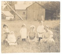 Image of PO.766.0010.2 - Women and children sitting in grass on Meadowbrook Farm.  Buildings in background.