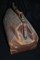 "Image of 028.041 - Lester Burn's Satchel suitcase. Brown length 16.5"" width 8.5"". Rough grained leather, corners reinforced with smooth leather corners, sewed on; button on bottom for scratch protection; full length brass metal strips or bands across top edges, with lock in center. Leather covered handle, attached top center. Lining of smooth yellow leather. Rectangle at bottom and half way up sides. Metal edges across top and part way down sides. Folds and closes to full length V across top. Hinged to open at top to same width as bottom rectangle."