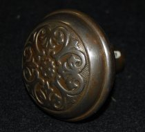 """Image of 074.178 - Doorknob from Meadowbrook Hotel.  round metal doorknob. Brass plate worn off. Embossed design in circle on top of knob.  Dome shaped top. 2 1/2"""" dia. 1"""" neck attached to bottom of knob."""