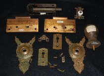 """Image of 075.065 - Door hardware from the Hop Ranch Hotel, Meadowbrook, Snoqualmie. 1. Wooden doorstops, turned, 3"""" long x 1.75"""" diameter at bottom. 2. Barrel bolt, bronzed with 2 screws, 4"""" long, with sliding bolt.  3. Door butt, 1 side only, for hinged doors (bronzed, embossed with scroll design). 1 7/8"""" w x 4"""" long, 4 screw holes, 2 screws. 4. Door butt, one side only, for hinged doors, bronzed, embossed scroll design. 1 7/8"""" w x 4"""" long. 4 screw holes, no screws.  5. Escutcheon plate for doorknob, embossed, triangle shape, extensions. 6. Escutcheons plate for doorknob, bronzed, scroll design embossed, triangle shape with 2 extended feet at bottom in center for doorknob. Green painted with worn spots showing bronze color. 5"""" long x 2"""" diameter 7. Keyhole escutcheon, ornamental bronze metal, one keyhole. 1 1/8"""" x 2.5"""" 8. 2 piece cupboard door bolt, bronze with white porcelain knob. 3"""" long x 1"""" wide. Wing tip ends with flower pattern embossed. 1""""x1"""" bolt open end. Embossed design.  All above escutcheons are polished bronze with a background a dark finish.   All above articles are pictured and described in Montgomery Ward Catalog, Fall & Winter, 1894 - 95, Guide No. 56, pages 368-375."""