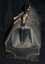 Image of 882.012 - Art Lee's black leather satchel with metal details used on his trip to the Rose Bowl game in 1937.  So. Pacific ticket attached