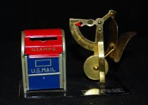 """Image of 074.487 - Advertisement souvenir, Stamp holder & letter weight measure, Falls Sheet Metal Work business memento FALLS SHEET METAL WORKS, Heating and Air Conditioning 109-1st Ave. So. Ph. 452-3826  Stamp folder is for roll of stamps to be enclosed in small red and blue street mailbox. Lift red top to put in stamps. Slot with sawtooth edge in front to tear stamps loose. Marked in silver with STAMPS and US Mail on front of box. Attached to black enameled metal plate stand. On right of box is upright weight with ounces on scale, indicator hand, and attached folded metal band for inserting letters to weigh. Attached to black metal base plate on right of box. measuring device is gold color. 3"""" high. Mail box 2 1/2"""" high. Base plate 2 1/4"""" wide x 4"""" long."""