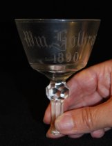 """Image of 075.542 - 1890 broken North Bend Saloon Wine Glass. Engraved William Holbrook.  Clear glass, bell shape with tapered sides, fluted cone to stem, attached to .5"""" size ball with octagonal cut around sides. 1.25"""" long stem, broken from base, with 7 cuts around stem. 4"""" tall x 2.75"""" diameter across the top.  This broken wine glass dated 1890 is from one of North Bend's early saloons, of which there were 13 at one time."""
