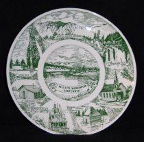 "Image of 015.225 - souvenir plate, commemorative. 1872-1972 Fall City, Washington- Centennial- plate color: Olive Green: 10"" across; depicting at the top- Mount Si, Cascade Mountains, clockwise Snoqualmie Falls, Community Church 1889, hop house (hop shed), 1877 Sternwheeler,"" Nellie""; First School House, Totem pole; center- Old Fall City - geographically the center of the Snoqualmie Valley. In the 1880s the Sternwheeler brought cargo from Seattle up the river to Fall City to supply the Valley needs. The little schoolhouse and the hop house (hop shed) are remembered historical sites and the totem pole is significant of the Snoqualmie Valley's Indian background. The Curch is still the ""Community"" Church of the area. Fall City Study Club organized 1922 federated-1925. Plate made at Kettlesprings Kilns; Alliance, Ohio. #2211-s"
