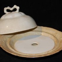 """Image of 074.320.A.B.C - 3-pc. china butter dish, Ironstone.  A. Bowl bottom of set. Raised design around edge, slightly scalloped groove for lid to fit inside. Stamped on bottom: Radisson      W.S. George    8173  Three tiny mold holes on underside near edge. Dish was originally white china. Now badly crazed with hairline cracks all over. size 7 1/2"""" diameter * 1 1/2"""" deep.  B. Inside drainer plate. Fits in bottom of bowl. Has raised foot on bottom of plate. Hole in center. Flat on topside. 4 1/2"""" diameter. White china slight discoloration around one edge.  C. Dome shaped lid with wider shoulders. Bow shaped handle in center top. Raised design around smaller part of dome. Hairline crack on one side. White China, some crazed cracks all over, little discoloration. 5 3/4"""" diameter. 3 1/4"""" deep.  This dish was 125 year old in 1972."""